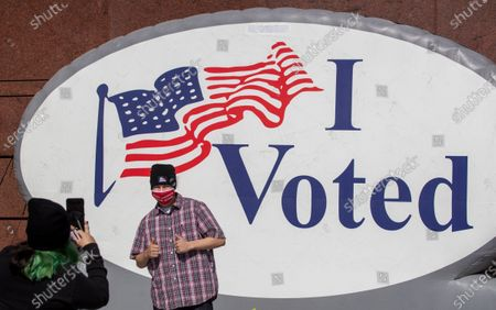 Stock Picture of Anthony Robles, of Garden Grove, poses as his sister, Daniela Robles, takes a photo of him after they voted early at the Honda Center on Monday, Nov. 2, 2020 in Anaheim, CA. (Allen J. Schaben / Los Angeles Times)