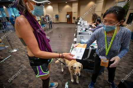 Hurley the dog watches as Shana Lakso, of Huntington Beach, left, takes a break from jogging to turn her ballot in to election worker Sihyang Lee, during early voting at the Huntington Beach Central Library Monday, Nov. 2, 2020. (Allen J. Schaben / Los Angeles Times)