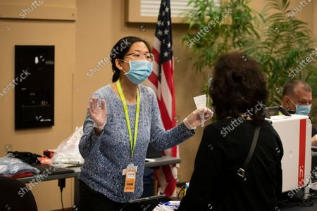 Election worker Sihyang Lee, left, helps a voter during early voting at the Huntington Beach Central Library Monday, Nov. 2, 2020. (Allen J. Schaben / Los Angeles Times)