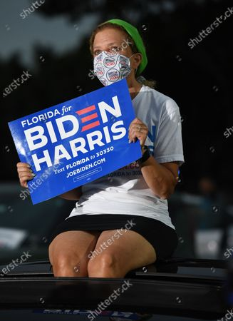 Congresswoman Debbie Wasserman Schultz is seen sitting on the roof of a car as Former US President Barack Obama speaks in support of Democratic presidential nominee Joe Biden during a election eve drive-in campaign rally at the Florida International University