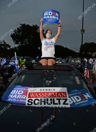 Stock Photo of Congresswoman Debbie Wasserman Schultz is seen sitting on the roof of a car as Former US President Barack Obama speaks in support of Democratic presidential nominee Joe Biden during a election eve drive-in campaign rally at the Florida International University
