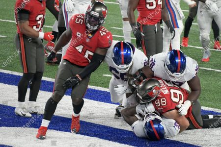 New York Giants' Wayne Gallman (22), bottom, scores a touchdown during the first half of an NFL football game against the Tampa Bay Buccaneers, in East Rutherford, N.J