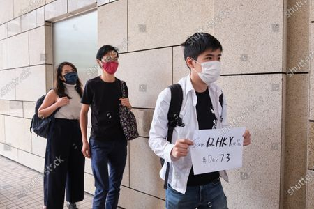 Activist Lester Shum (R) wearing a face mask holds a placard that says Save 12 HK Youths Day #73 as he arrives at West Kowloon Magistrates' Court  with Eddie Chu (C) and Gwyneth Ho (L). 26 Hong Kong pro-democracy activists including media tycoon Jimmy Lai and Joshua Wong appear in court after being charged with participating in or inciting others to take part in an illegal assembly related to a banned June 4 vigil commemorating the Tiananmen Sqaure crackdown.
