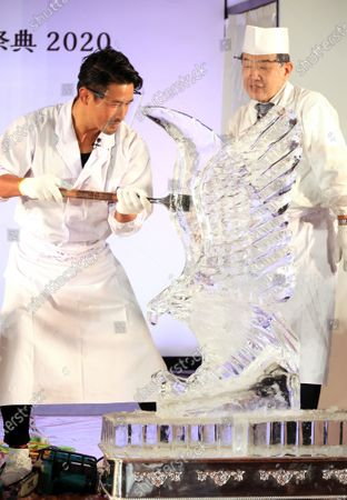 """Former K-1 champion Masato (L) shaves ice cube to make an ice sculpture of an eagle at a traditional craftwork exhibition """"Monozukuri - A Celebration of Japanese Artisanal Tecjniques"""" in Tokyo while master of ice sculpture Japanese restaurant chef Hideo Kase (R) looks on on Tuesday, November 3, 2020."""