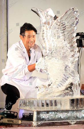 """Stock Picture of Former K-1 champion Masato shaves ice cube to make an ice sculpture of an eagle at a traditional craftwork exhibition """"Monozukuri - A Celebration of Japanese Artisanal Tecjniques"""" in Tokyo on Tuesday, November 3, 2020."""