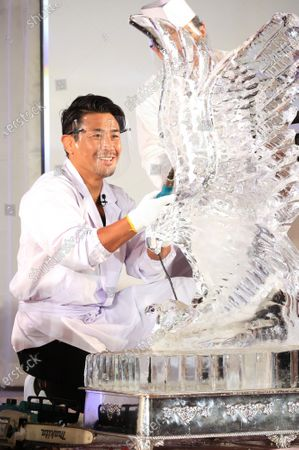 """Stock Image of Former K-1 champion Masato shaves ice cube to make an ice sculpture of an eagle at a traditional craftwork exhibition """"Monozukuri - A Celebration of Japanese Artisanal Tecjniques"""" in Tokyo on Tuesday, November 3, 2020."""