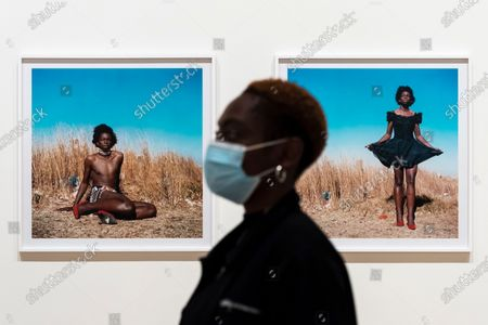 """A staff member next to """"Miss D'vine I, Yeoville, Johannesburg"""", 2007 by Zanele Muholi. Preview of the first major UK exhibition by South African visual activist Zanele Muholi at Tate Modern. 260 photographs document black lesbian, gay, trans, queer and intersex lives in South Africa. The show runs 5 November to 7 March 2021, but will be interrupted by England's coronavirus pandemic lockdown currently due to last 5 November to 2 December."""