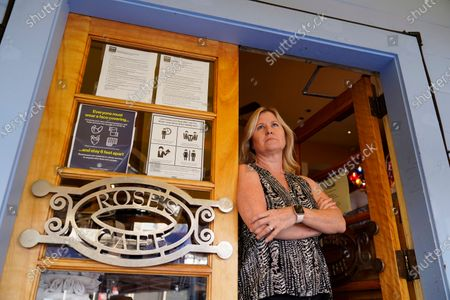 """Laurie Thomas poses at the entrance to her Rose's Cafe restaurant, Sept. 28, 2020, in San Francisco. California's landmark ballot measure that keeps a lid on property taxes by tying them to the most recent purchase price is facing one of the biggest challenges in its 42-year history. Proposition 15 Tuesday's ballot would reassess commercial and industrial properties every three years. Thomas, who owns two restaurants in San Francisco, said Proposition 15 would be """"one more nail in the coffin"""" of her industry"""