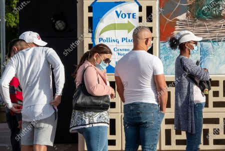 Voters wait in line to cast their votes at the John F. Kennedy Library in Hialeah, Florida, USA, 03 November 2020. Americans vote on Election Day to choose between re-electing Donald J. Trump or electing Joe Biden as the 46th President of the United States to serve from 2021 through 2024.