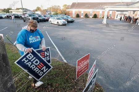 Lee Jones sets up signs while voters line up waiting to cast their ballots at the polling place at the Bellevue Church of Christ  in Nashville, Tennessee on 03 November 2020. Americans vote on Election Day to choose between re-electing Donald J. Trump or electing Joe Biden as the 46th President of the United States to serve from 2021 through 2024.