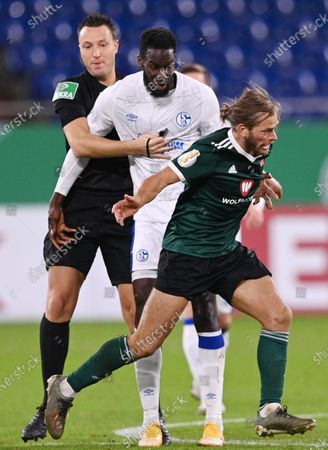 Referee Sven Jablonski tries to hold back Salif Sane (C) of Schalke from Kristian Boehnlein of Schweinfurt during the German DFB Cup first round soccer match between 1. FC Schweinfurt 05 and FC Schalke 04 at Veltins Arena in Gelsenkirchen, Germany, 03 November 2020.