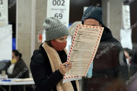 Pair of voters at Frank McCourt High School,on New York's Upper West Side, survey their ballots on Election Day