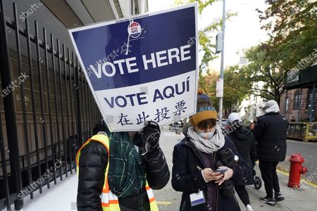 Poll workers direct voters outside Frank McCourt High School, on New York's Upper West Side