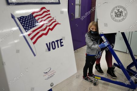 Holden Middleton joins her mom at the voting booth at Frank McCourt High School, on New York's Upper West Side, . An unprecedented Election Day has gotten under way in New York, with polls now open statewide