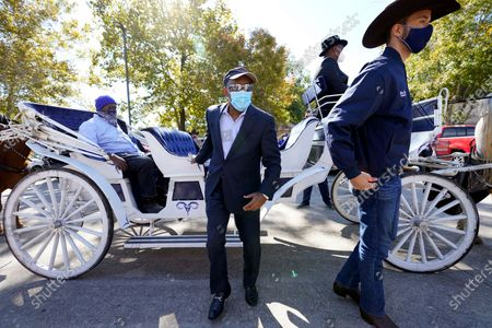 Stock Photo of Houston Mayor Sylvester Turner, center, and Harris County Clerk Chris Hollins, right, arrive a voting site, in Houston