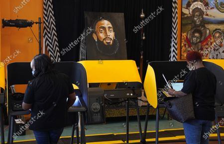 Portrait of the late rapper and entrepreneur Nipsey Hussle stands behind voters as they complete their ballots at the Hot and Cool Cafe, in the Leimert Park section of Los Angeles