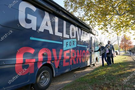 Missouri Auditor and Democratic gubernatorial candidate Nicole Galloway opens the door of her campaign bus followed by her husband, Jon, and sons Benjamin and William after stopping to talk with voters outside a polling place, in St. Louis. Galloway is challenging incumbent Republican Gov. Mike Parson