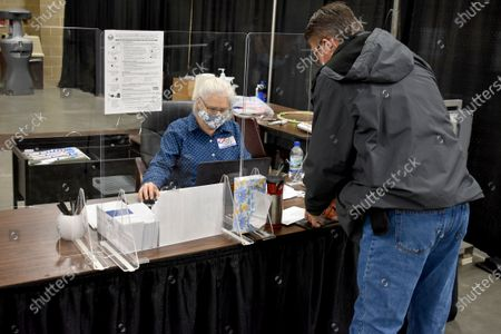 An election worker helps a voter with his ballot on at the MetraPark events center in Billings, Mont. Montana voters were picking candidates for president, Senate, House, governor and other races