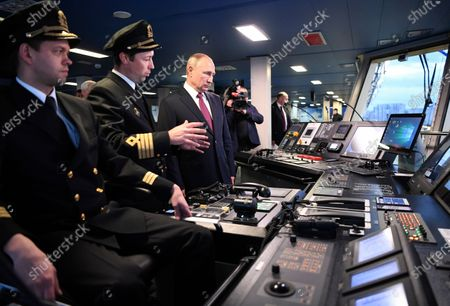"""Russian President Vladimir Putin, center, visits the captain's bridge of the newly built diesel-electric icebreaker """"Viktor Chernomyrdin"""" in St. Petersburg, Russia, . Putin said that Russia will expand its fleet of icebreakers as part of its efforts to develop the Arctic territories"""