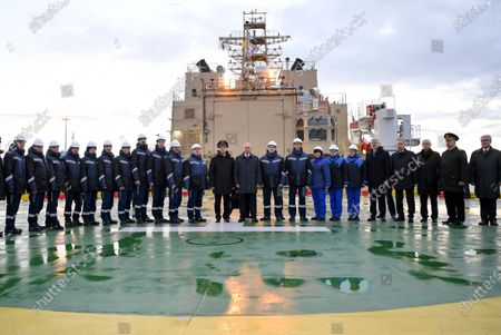 """Stock Picture of Russian President Vladimir Putin, center, poses for a photo as he visits the newly built diesel-electric icebreaker """"Viktor Chernomyrdin"""" in St. Petersburg, Russia, . Putin said that Russia will expand its fleet of icebreakers as part of its efforts to develop the Arctic territories"""