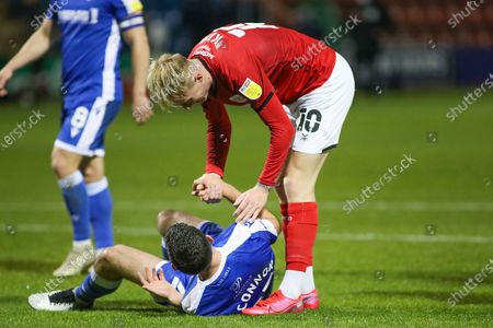 Stock Image of Crewe Alexandra midfielder Charlie Kirk (10) helps Gillingham FC midfielder Thomas O'Connor (21) up during the EFL Sky Bet League 1 match between Crewe Alexandra and Gillingham at Alexandra Stadium, Crewe