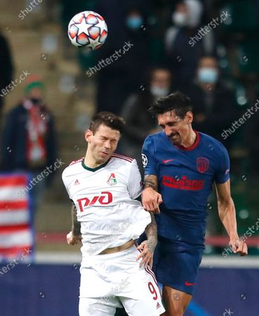 Lokomotiv's Fyodor Smolov, left, and Atletico Madrid's Stefan Savic challenge for the ball during the Champions League Group A soccer match between Lokomotiv Moscow and Atletico Madrid in Moscow, Russia