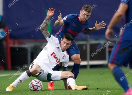 Lokomotiv's Fyodor Smolov, left, and Atletico Madrid's Kieran Trippier challenge for the ball during the Champions League Group A soccer match between Lokomotiv Moscow and Atletico Madrid in Moscow, Russia