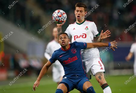Atletico Madrid's Renan Lodi, left, and Lokomotiv's Fyodor Smolov challenge for the ball during the Champions League Group A soccer match between Lokomotiv Moscow and Atletico Madrid in Moscow, Russia