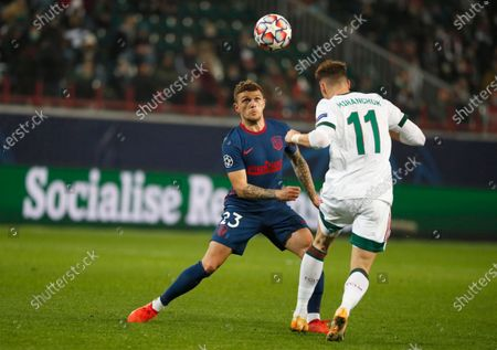 Atletico Madrid's Kieran Trippier, left, and Lokomotiv's Anton Miranchuk challenge for the ball during the Champions League Group A soccer match between Lokomotiv Moscow and Atletico Madrid in Moscow, Russia