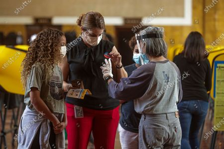 Stock Photo of Dyana Elam, center, who came to vote with her children Jackson Love, 11, left, and Jordan Love, 11, gets I Voted sticker from poll worker Heizel Acuna at a polling station located at Union Station on Tuesday, Nov. 3, 2020 in Los Angeles, CA. (Irfan Khan / Los Angeles Times)