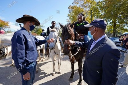 Stock Picture of Harris County Clerk Chris Hollins, left, and Houston Mayor Sylvester Turner pet the horses of Eboni Price, second from right, and Cornelius Ates outside a voting site, in Houston