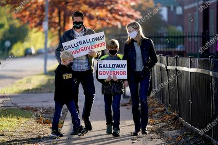 Stock Photo of Missouri Auditor and Democratic gubernatorial candidate Nicole Galloway walks back to her campaign bus with her husband, Jon, and boys Benjamin, left, and William after greeting voters outside a polling place, in St. Louis. Galloway is challenging incumbent Republican Gov. Mike Parson