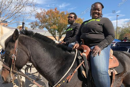"""Stock Picture of Eboni Price, right, used a different form of transportation to get to her polling site in Houston, Texas, her trusty horse Moon. """"My people went through a lot of things to have the right to vote,"""" Price said. """"I can exercise my right to vote on horseback so I'm riding to vote."""" Price, who is also studying to be a veterinarian, said she voted for Kanye West in the presidential race"""