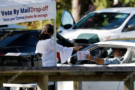 A poll worker (L) takes a drive-in ballot from voter in the 2020 US presidential election at the Robert L. Gilder Elections Service Center in Tampa, USA, 03 November 2020. Americans vote on Election Day to choose between re-electing Donald J. Trump or electing Joe Biden as the 46th President of the United States to serve from 2021 through 2024.