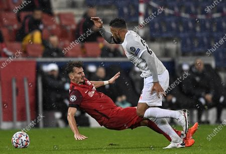 Salzburg's Mergim Berisha, left, and Bayern's Corentin Tolisso, right, challenge for the ball during the Champions League group A soccer match between RB Salzburg and Bayern Munich in Salzburg, Austria