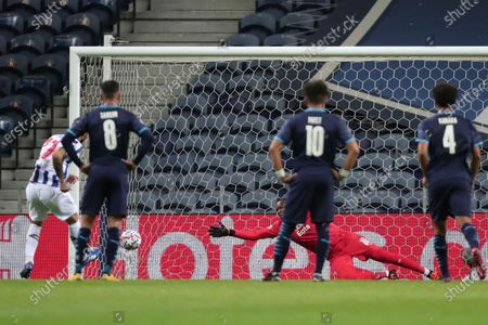 Marseille's goalkeeper Steve Mandanda, background center, fails to stop Porto's Sergio Oliveira goal from the penalty spot during the Champions League group C soccer match between FC Porto and Olympique de Marseille at the Dragao stadium in Porto, Portugal