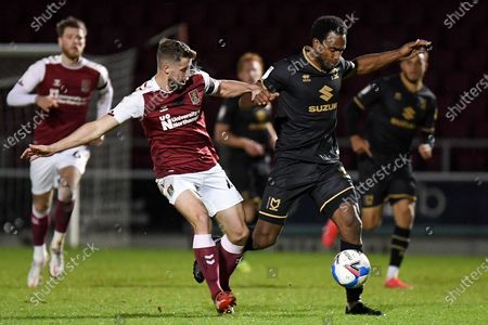 Milton Keynes Dons forward Cameron Jerome (35) battles for possession  with Northampton Town midfielder Jack Sowerby (4) during the EFL Sky Bet League 1 match between Northampton Town and Milton Keynes Dons at the PTS Academy Stadium, Northampton