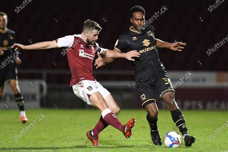 Northampton Town midfielder Jack Sowerby (4) comes in to tackle Milton Keynes Dons forward Cameron Jerome (35) during the EFL Sky Bet League 1 match between Northampton Town and Milton Keynes Dons at the PTS Academy Stadium, Northampton