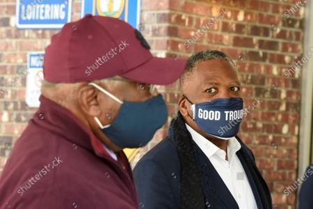 Steve Benjamin, mayor of Columbia, S.C., right, looks on as U.S. House Majority Whip Jim Clyburn, left, speaks with a voter outside a polling place, in Columbia, S.C
