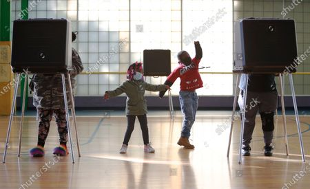 Stock Picture of Karrihanna Stone (L-C), age 5 and Deonte Harris (R-C), age 8, entertain themselves while their mother Cashondra Davis (L) and grandmother Stephanie Davis (R) vote at a polling location at the Zelma Watson George Community Center in Cleveland Ohio, USA, 03 November 2020. Americans vote on Election Day to choose between re-electing Donald J. Trump or electing Joe Biden as the 46th President of the United States to serve from 2021 through 2024.