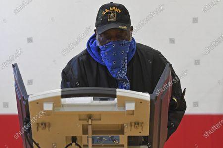 Robert Powell casts his ballot at Alliance High School, in Alliance, Ohio