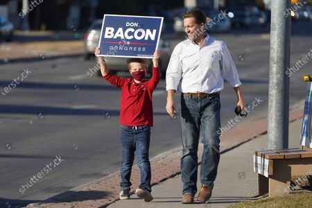 Sen. Ben Sasse, R-Neb., arrives with his son Breck on Election Day, to join Rep. Don Bacon, R-Neb., for a sign-waving event in Omaha, Neb. Sen. Sasse is facing a challenge by Democrat Chris Janicek, while Bacon is in a competitive race with his challenger, Democrat Kara Eastman