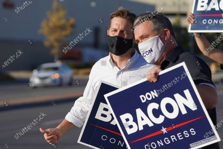 Stock Photo of Sen. Ben Sasse, R-Neb., left, joins Rep. Don Bacon, R-Neb., during a sign-waving event in Omaha, Neb., on Election Day, . Sen. Sasse is facing a challenge by Democrat Chris Janicek, while Bacon is in a competitive race with his challenger, Democrat Kara Eastman