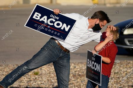 Stock Image of Sen. Ben Sasse, R-Neb., attends to his son Breck on Election Day, during a sign-waving event with Rep. Don Bacon, R-Neb., in Omaha, Neb. Sen. Sasse is facing a challenge by Democrat Chris Janicek, while Bacon is in a competitive race with his challenger, Democrat Kara Eastman