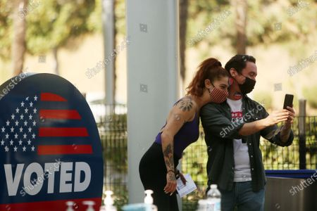 Yael Vengroff, left, and Paul Piane, right, take a selfie after voting at the Hollywood Bowl Vote Center in Hollywood on Tuesday, Nov. 3, 2020 in Los Angeles, CA.(Dania Maxwell / Los Angeles Times)