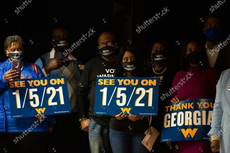 Stock Image of Family and supporters hold runoff signs as Democratic US Senate candidate Rev. Raphael Warnock speaks during an Election Night event in Atlanta, Georgia, USA, 03 November 2020. Democratic Senate candidate Rev. Raphael Warnock is running in a special election against a crowded field, including U.S. Sen. Kelly Loeffler (R-GA), who was appointed by Gov. Brian Kemp to replace Johnny Isakson at the end of last year. Georgia is the only state with two Senate seats on the 03 November ballot.