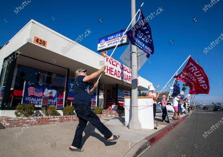 Pres. Trump supporter Steve Martin, left, of Westminster, joins fellow supporters as he dances and cheers on passing motorists in front of the Republican Party headquarters on election day Tuesday, Nov. 3, 2020 in Newport Beach. (Allen J. Schaben / Los Angeles Times)