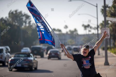 Pres. Trump supporter Steve Martin, of Westminster, joins fellow supporters as he dances and cheers on passing motorists in front of the Republican Party headquarters on election day Tuesday, Nov. 3, 2020 in Newport Beach. (Allen J. Schaben / Los Angeles Times)