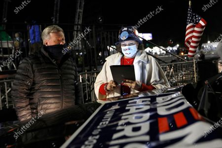 Stock Picture of Wilmington, Delaware-Nov. 3, 2020-Tom Cook looks over at Lydia Massey from Dover, DE. iPad for election night results at a drive-in rally at Chase Center in Wilmington, Delaware, on Nov.3, 2020. (Carolyn Cole / Los Angeles Times)
