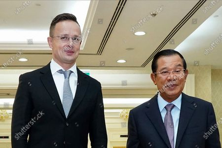 Stock Photo of Hungarian Foreign Minister Peter Szijjarto, left, poses with Cambodian Prime Minister Hun Sen for a photo prior to a meeting at Peace Palace in Phnom Penh, Cambodia, . Szijjarto tested positive for the coronavirus after arriving in Thailand for an official visit, Thai and Hungarian officials said Wednesday, Nov. 4, 2020